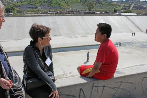 Una miembro del Consejo de Líderes Religiosos de Los Ángeles habla con Oscar, que creció en el área metropolitana de Los Ángeles, pero quien, hace año y medio, vino a México con sus padres, que fueron deportados. La familia ahora vive en Chilpancingo, un barrio marginal cerca de Tijuana. Foto de Janet Kawamoto
