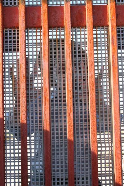 """Una gruesa malla de metal superpuesta al enrejado del muro en el llamado """"Parque de la Amistad"""" impide todo contacto físico y la mayor parte del contacto visual entre ambos lados de la frontera mexicoamericana. A unos 15 metros por el lado de EE.UU. hay una segunda cerca que se abre sólo por breves períodos los fines de semana para permitir que personas de cada lado del muro conversen con sus familiares y amigos del otro lado. Foto de Janet Kawamoto."""