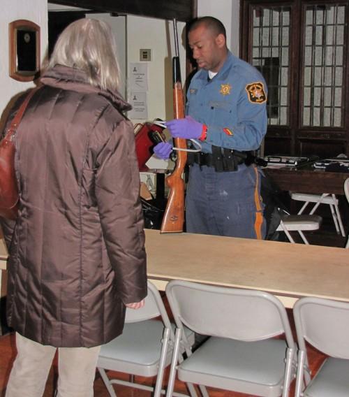 El detective Craig Brooks, de la Oficina del Alguacil del Condado de Morris, examina un arma que entregaron durante la recuperación anónima de armas auspiciada por la iglesia episcopal de San Pedro en Morristown, Nueva Jersey. Foto de Sharon Sheridan.