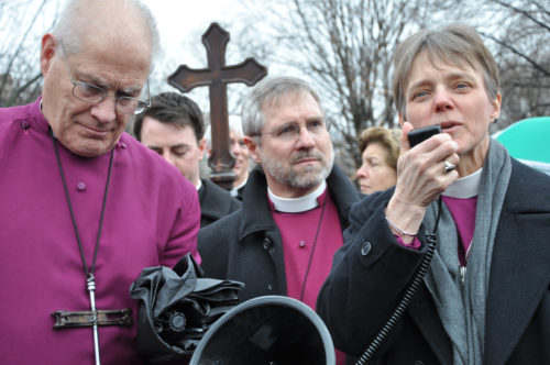 Episcopal Diocese of Washington Bishop Mariann Edgar Budde recites prayers at the first Way of the Cross station March 21 in Lafayette Square in Washington, D.C. Diocese of Connecticut Bishop Suffragan James Curry, left, and Connecticut Bishop Ian Douglas listen. ENS photo/Mary Frances Schjonberg