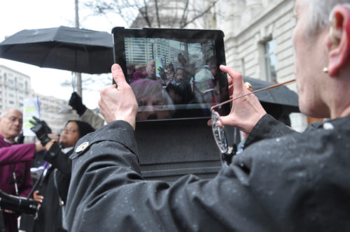 Bishop Suffragan Mary Glasspool of Los Angeles captures video of Diocese of Massachusetts Bishop Suffragan Gayle Harris leading prayers at one of the Way of the Cross stations. ENS photo/Mary Frances Schjonberg
