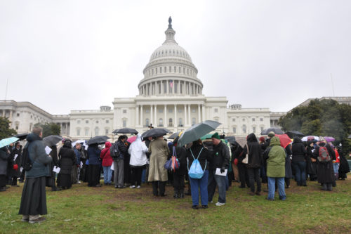 The 13th and 14th stations on the Way of the Cross were on the wet, muddy lawn of the U.S. Capitol. ENS photo/Mary Frances Schjonberg