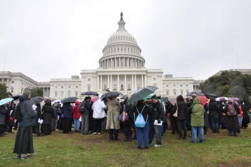 Las 13ª. Y 14ª. estaciones del Via crucis fueron en el césped húmedo y lodoso del Capitolio federal. Foto de Mary Frances Schjonberg para ENS.