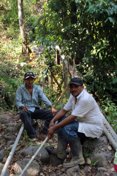 Líderes comunitarios en El Carmen sentados junto a la tubería que lleva el agua de manantial por una pendiente de 90 metros hasta los hogares de 26 familias en El Carmen. Foto de Lynette Wilson para ENS.