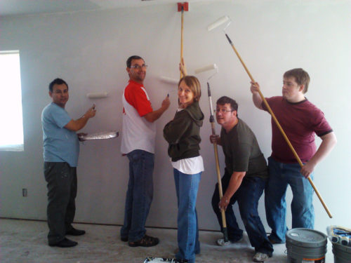 A group of Episcopalians helps paint the interior of Rose Cottage. Photo: Peggy Ralston