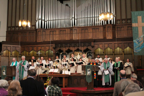The Rev. John Paddock and the Rev. Rodney Kennedy, far left, are joined by a combined choir of both congregations for the first worship service together. Photo/Greg Sexton