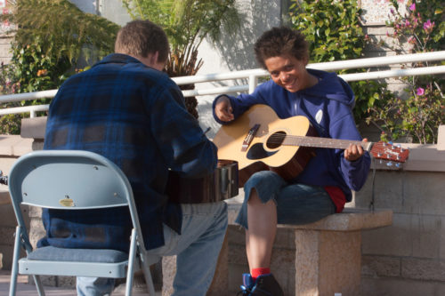 Amber, one of the participants in the Taking Music to the Streets program at the Episcopal Church Center in Ocean Beach, California, strums a guitar during a lesson with volunteer teacher Packy Bergquist. The program offers free weekly music lessons to homeless youth. Once a youth returns three times to the program, he or she receives a free instrument. As trust builds, volunteers assist the youth with safe living situations, education, job training and general life skills. Photo/Jeffrey Sitcov