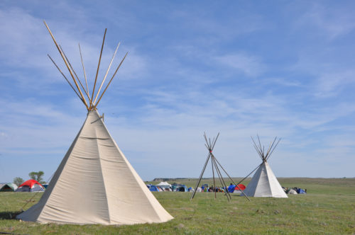 """Close to 600 pilgrims, mostly aged 18 to 35, came to the Taizé """"pilgrimage of trust on earth"""" on the prairie at Red Shirt Table, South Dakota in the Pine Ridge Sioux Reservation. They pitched their modern-day tents around some more traditional ones. Photo: Mary Frances Schjonberg/Episcopal News Service"""
