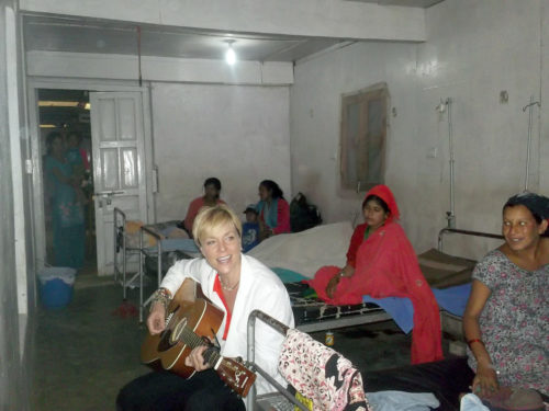 Karin Feltman plays guitar at a hospital in Dadeldhura, Nepal, during a visit there in May 2012. Feltman, a member of St. Margaret's, Lawrence, Kansas, will become a long-term missionary there beginning in 2014.
