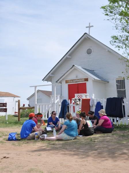 Un pequeño grupo de peregrinos de Taizé discuten pasajes del estudio bíblico matutino (Isaías 43:18-9 e Isaías 48:6-8) el 25 de mayo delante de la iglesia episcopal de Cristo en Red Shirt Table, Dakota del Sur, mientras los sacos de dormir se ventilan en el fresco aire de la mañana. Los 600 peregrinos, la mayoría entre 18 y 35 años de edad, dedicaron una parte importante de cada día al estudio bíblico en grupos grandes y pequeños. Foto de Mary Frances Schjonberg para ENS.