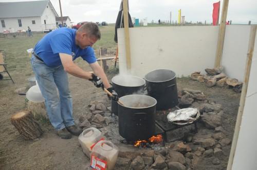 """Chris Soukup revuelve una olla de carne de búfalo para el último almuerzo de la """"peregrinación de la confianza en la tierra"""" de Taizé en Red Shirt Table, en la reserva sioux de Pine Ridge, Dakota del Sur. El consejo tribal de la nación oglala lakota donó dos búfalos para alimentar a los casi 600 peregrinos. El 27, Soukup y su esposa, Mary, que asistieron a la catedral del Calvario en Sioux, se unieron a Twila Two Bulls para cocinar lo que había quedado del día anterior. Foto de Mary Frances Schjonberg para ENS."""
