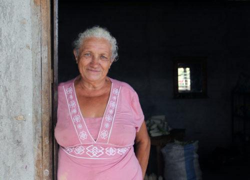 Carmen Milagro Flores, una de los dirigentes comunitarios de La Anémona, de pie a la puerta de su casa. Como líder, Flores dice sentirse responsable de otros miembros de la comunidad. Foto de Lynette Wilson para ENS.