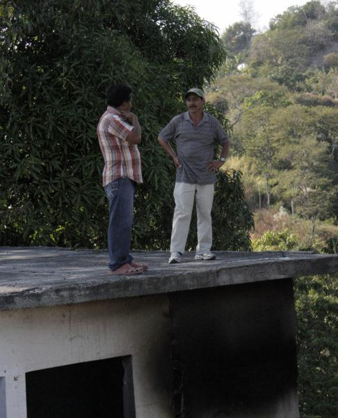 José Manuel Muñoz, a la derecha, y Benjamín Pérez, residentes de La Anémona, de pie sobre el techo de una de las casas abandonadas de la comunidad donde habían vivido durante 36 años. El huracán Ida obligó a los residentes a abandonar sus casas en 2009. Foto de Lynette Wilson para ENS.