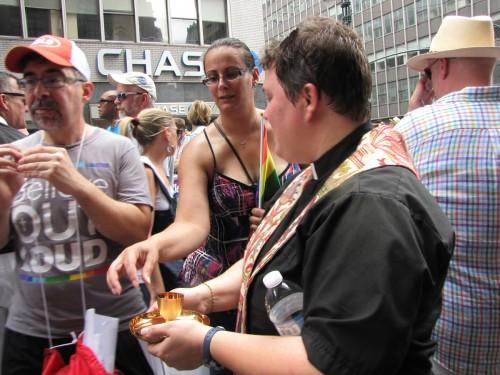 La Rda. Megan Sanders, rectora interina de la iglesia de San Andrés en Staten Island, reparte la comunión el 30 de junio en la eucaristía ofrecida por el capítulo de Integrity del área metropolitana de Nueva York a los manifestantes del Desfile del Orgullo Homosexual que no tenían oportunidad de asistir a la iglesia antes de participar en el evento a lo largo de la Quinta Avenida. Foto de Sharon Sheridan para ENS.
