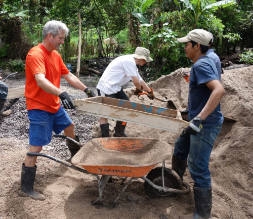 Volunteers shovel and sift sand to remove stones in preparation for mixing cement. [left to right: Clarke Bailey, Peter Kizer (in background), Bridges trip leader Hugo Gonzales]. Photo: Paul Cantwell