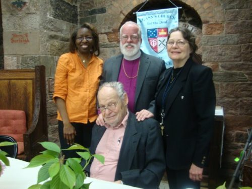 """Pictured with the Rev. Henry Buzzard, seated, are, from left, lay leader Melissa Inniss, New York Bishop Andrew Dietsche and lay leader Evelyn Schafer at St. Ann's Church for the Deaf. Buzzard, who just celebrated his 90th birthday, is retired priest of St. Ann's and was the first deaf and blind priest in America. He is one of the authors of """"Thomas Gallaudet Apostle to the Deaf."""""""
