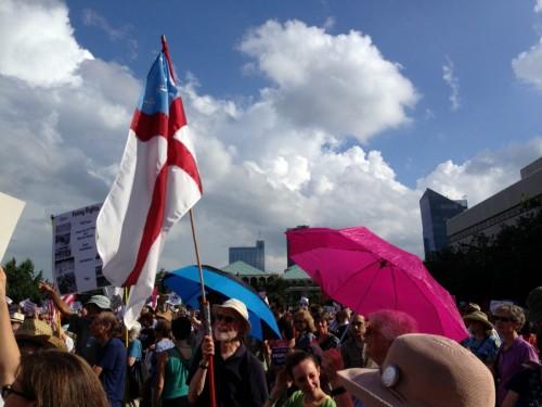 Phil Rees, de la iglesia episcopal Capilla de la Cruz, en Chapel Hill, Carolina del Norte, sostiene la bandera del ministerio universitario de la Iglesia durante una concentración del Lunes Moral en Raleigh. Foto de Lisa Fischbeck.