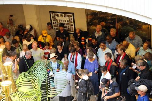 Manifestantes que se ofrecieron voluntariamente para ser arrestados por desobediencia civil como parte de las protestas del Lunes Moral en Raleigh, Carolina del Norte, esperan dentro del edificio del gobierno estatal. Foto de Summerlee Walter/Diócesis Episcopal de Carolina del Norte.