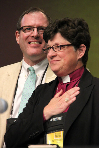 Evangelical Lutheran Church in America Presiding Bishop-elect Elizabeth A. Eaton  and her husband, the Rev. Conrad Selnick, an Episcopal priest, react shortly after her Aug. 14 election. Photo: ELCA