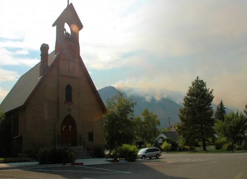 El incendio de Beaver Creek puede verse en las montañas que dominan la iglesia episcopal Emanuel en Hailey, Idaho. Foto de Michael Mathewson.