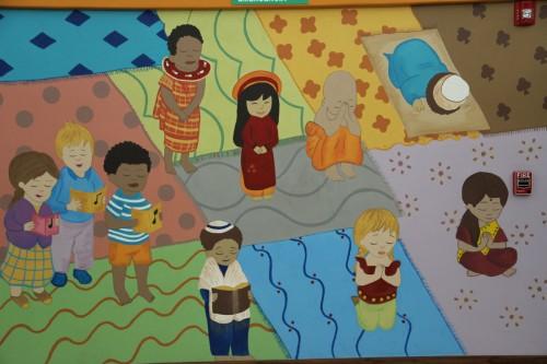 Un mural en el salón de multiusos del Hogar Escuela en Heredia muestra a todas las grandes religiones del mundo, haciendo obvio que la escuela está a disposición de todos. Foto de Lynette Wilson para ENS.