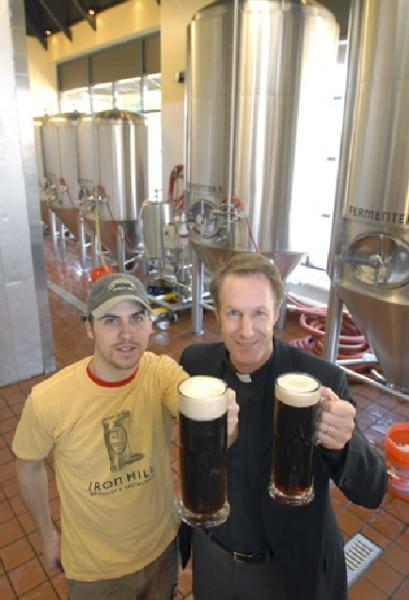 El Rdo. David Peck (a la derecha) y Chad Rieker, maestro cervecero de la destilería de cerveza Iron Hill, en Lancaster, Pensilvania, levantan sus jarras de la cerveza negra que fabrican en el lugar. Foto de Richard Hertzler