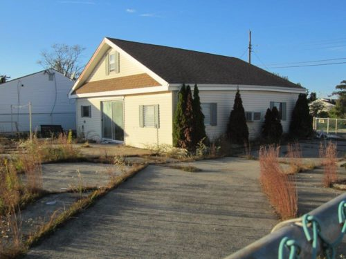 The outsides of many abandoned homes, such as this one in Little Egg Harbor, do not look as if they were damaged by Sandy. However, flooding has wrecked their interiors. Photo: Church of the Holy Spirit