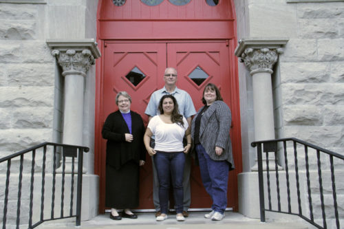 The Rev. Dorothy Hartzog, Lizette Green-Medina, Kendall Welsh and Jim Johnson standing on the steps of Trinity Episcopal Parish in downtown Clarksville, Tennessee. In 2012, Trinity offered space to Nashville CARES, a nonprofit organization that offers services to people living with HIV and AIDS. Photo: Lynette Wilson/Episcopal News Service