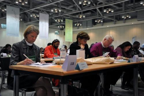 Miembros de la delegación oficial de la Iglesia Episcopal a la Asamblea General del CMI examinan un documento durante una de las sesiones plenarias. Ellos son (de izquierda a derecha) la Rda. Margaret Rose, la Rda. Consuela Sánchez, el obispo Dean Wolfe y Jasmine Bostock. Foto de Matthew Davies para ENS.