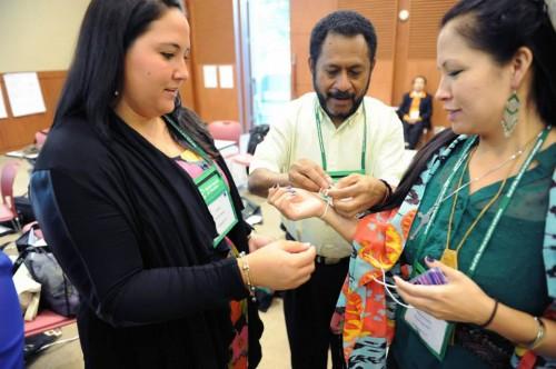 De izquierda a derecha, Jasmine Bostock, de la Diócesis Episcopal de Hawái; Leonard Imbiri, secretario general del Consejo de Costumbres de Papúa, y Sarah Eagle Heart, misionera de la Iglesia Episcopal para los indígenas, se ayudan mutuamente a atarse un brazalete de oración por la unidad. Foto del CMI.