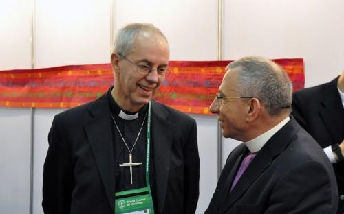 """El arzobispo de Cantórbery, Justin Welby (a la izquierda) y el obispo Munib Younan, de la Iglesia Evangélica Luterana de Palestina y Jordania comparten un momento luego de firmar la ratificación de los líderes de la fe a """"Bienvenido el extranjero"""". Foto de Matthew Davies para ENS."""