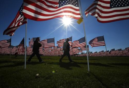 Dos individuos pasan junto a algunas de las dos mil trece banderas de Estados Unidos que ondean en el Campo de Recuperación [Healing Field] de Aurora, Illinois, el 10 de noviembre de 2013. El Día de los Veteranos se conmemora el 11 de noviembre. Foto de Jeff Haynes para REUTERS.