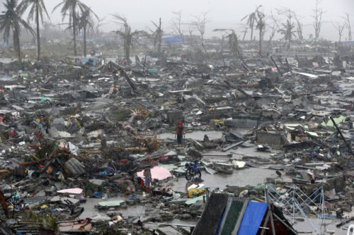 People stand among debris and ruins of houses destroyed after Super Typhoon Haiyan battered Tacloban city in central Philippines November 10, 2013. Haiyan, one of the most powerful storms ever recorded killed at least 10,000 people in the central Philippines province of Leyte, a senior police official said on Sunday, with coastal towns and the regional capital devastated by huge waves. Super typhoon Haiyan destroyed about 70 to 80 percent of the area in its path as it tore through the province on Friday, said chief superintendent Elmer Soria, a regional police director. Photo: REUTERS/Erik De Castro