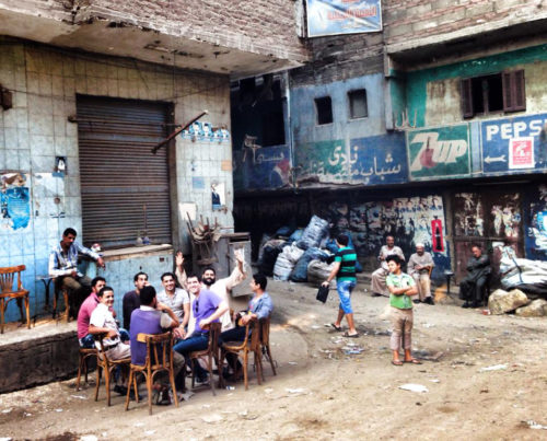 """Gavin Rogers shares drinks with residents from """"Garbage City,"""" or the Zabaleen community. His guide, Wael Fahim, is seated on the far left, wearing a white shirt. Photo: Matthew Aragones"""