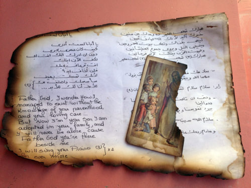Sections of a prayer book and art from burned churches in Suez. Photo: Gavin Rogers
