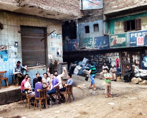 """Gavin Rogers comparte unos tragos con vecinos de """"la ciudad de la basura"""" o la comunidad Zabaleen. Su guía, Wael Fahim, de camisa blanca, aparece sentado a la extrema izquierda. Foto de Matthew Aragonés."""