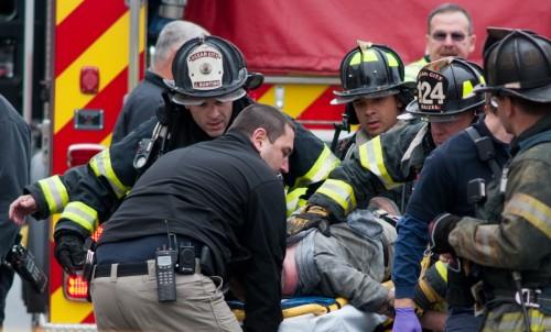 Miembros del Departamento de Bomberos de Ocean City llevan a una de las víctimas extraídas del edificio en llamas hasta una ambulancia que espera en la avenida Baltimore, Ocean City, el martes 26 de noviembre por la mañana. Foto de Grant L. Gursky.