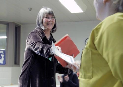 Kathy McGregor, directora del Proyecto de Relatos de Prisión del Noroeste de Arkansas, presenta un certificado a una de las 12 narradoras  que participaron de la representación de Relatos de adentro hacia afuera el 14 de noviembre en el Centro Correccional Comunitario del Noroeste de Arkansas en Fayetteville. Foto de Lynette Wilson para ENS.