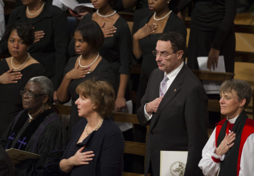 Diocese of Washington Bishop Mariann Edgar Budde and Washington, D.C. Mayor Vincent Grey place their hands over their heart during the singing of the U.S. National Anthem during a memorial service for former South African President Nelson Mandela at Washington National Cathedral on Dec. 11. Vice President Joe Biden and Presiding Bishop Katharine Jefferts Schori, led the national service for Mandela, held in conjunction with the South African Embassy, and featuring a host of dignitaries, elected officials, and civil rights leaders. Photo: Cliff Owen, Associated Press