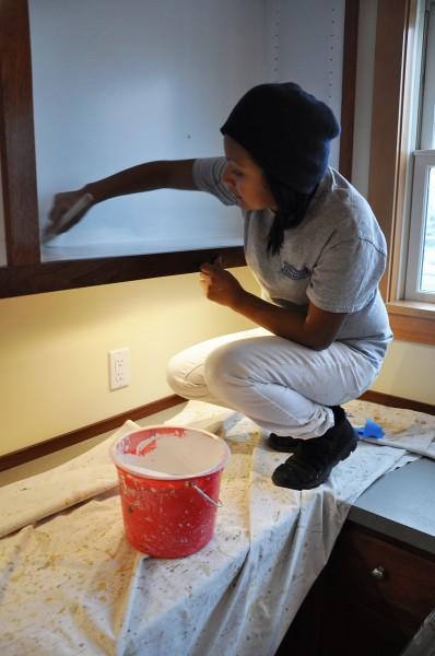 La pintora Erika Martínez da los últimos toques en el interior de unos armarios en el área de oficinas de la iglesia episcopal de Todos los Santos en Bay Head, Nueva Jersey. Foto de Mary Frances Schjonberg para ENS.