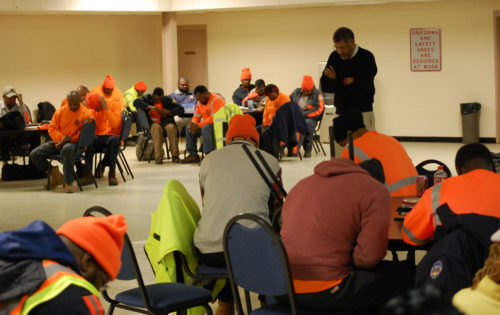 Bishop Rob Wright leads a prayer for sanitation workers before their shift begins. Photo: Don Plummer/Diocese of Atlanta