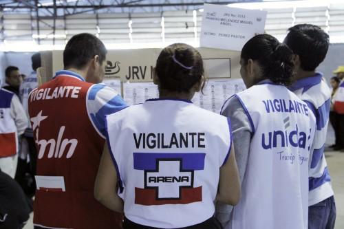 Tres vigilantes, en representación de los tres principales partidos políticos, sirvieron en cada puesto individual de votación, además de los trabajadores electorales. Foto de Lynette Wilson para ENS.