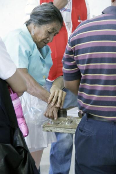 Una mujer mete el dedo en un tarro de pintura luego de votar en las elecciones presidenciales de El Salvador el 2 de febrero. Sears ofreció el 2 de febrero un 20 por ciento de descuento a los votantes con el dedo manchado de pintura. Foto de Lynette Wilson para ENS.
