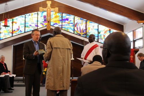 Dan Dykstra presents a healing blanket to Mario Luwal, elder of the Dinka community, as a gift from St. Thomas Episcopal Church in Louisville. Photo: Brian Funk-Kinnaman, Diocese of Kentucky staff