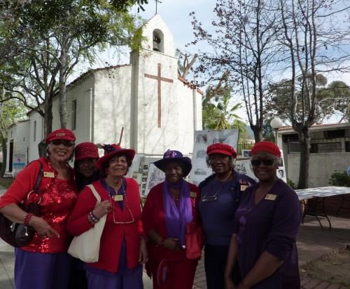 Gail McKinnon (extrema izquierda) con Gloria Huffman (a su lado) miembros de San Bernabé que trajeron al desfile y a la iglesia a sus hermanas del capítulo Rosas Nubias del Nilo de la Sociedad del Sombrero Rojo. Foto de Keith Yamamoto.
