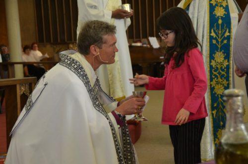 Obispo David Rice da la Sagrada Eucaristía a uno de los miembros más jóvenes de la Diócesis de San Joaquín. Foto: Richard Schori