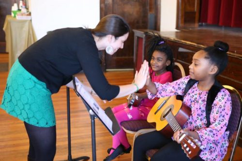 Jillian Smith, an Episcopal Service Corps intern who serves part time at All Saints, shows positive encouragement during music classes.