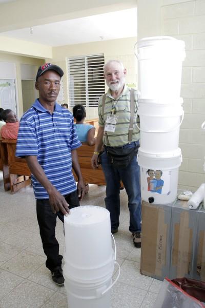 Paul Gutmann y Domingo de la Rosa presentan el sistema de filtración de agua de tres cubos. Foto: Lynette Wilson/Episcopal News Service