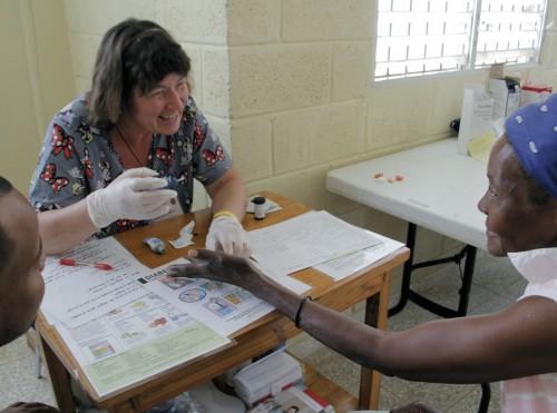 Rita Bush, una consejera especialista en nutrición y diabetes, realiza pruebas de azúcar en la sangre de un paciente durante el primer día de la clínica médica en Santo Tomas en Gautier. Foto: Lynette Wilson / Episcopal News Service