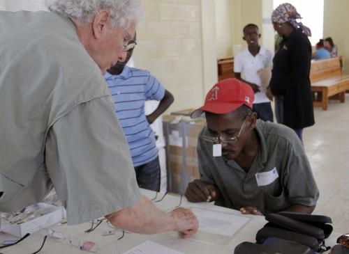 John C. Cain, Jr. ayuda a un hombre elegir anteojos de lectura en la clínica médica de la Iglesia Episcopal Santo Tomás en Guatier, República Dominicana. Caín es parte de un equipo médico del estado de Nueva York que está dirigiendo una clínica médica del 3 al 7 de marzo en la iglesia. Foto: Lynette Wilson / Episcopal News Service